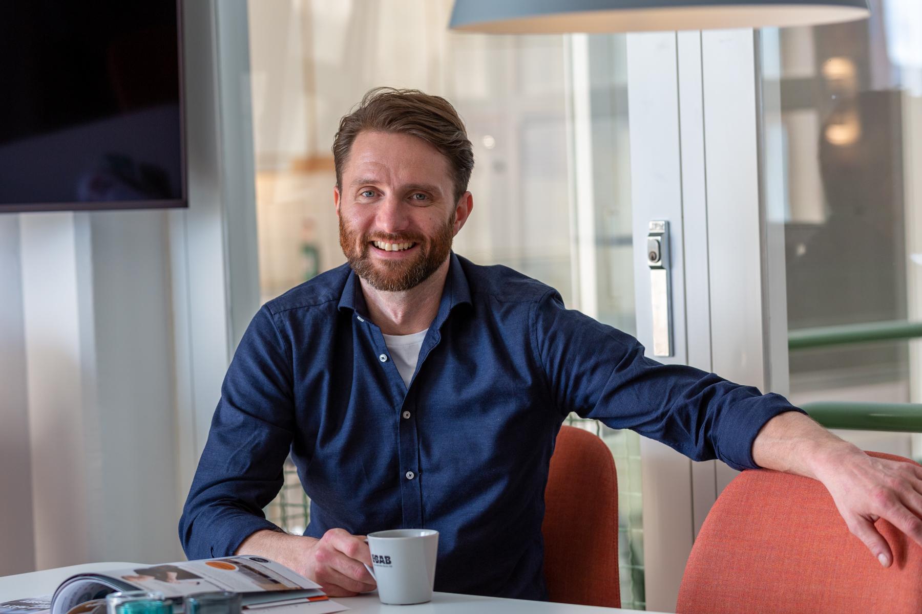 Fredrik Olsson sitter med en kaffemugg i lunchrummet och ler mot kameran.